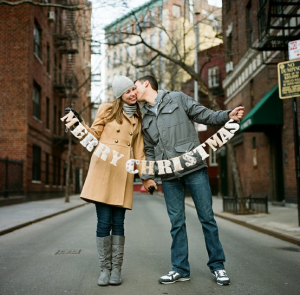 couplewithsign 300x295 Ideas For Cute & Clever Christmas Card Photos